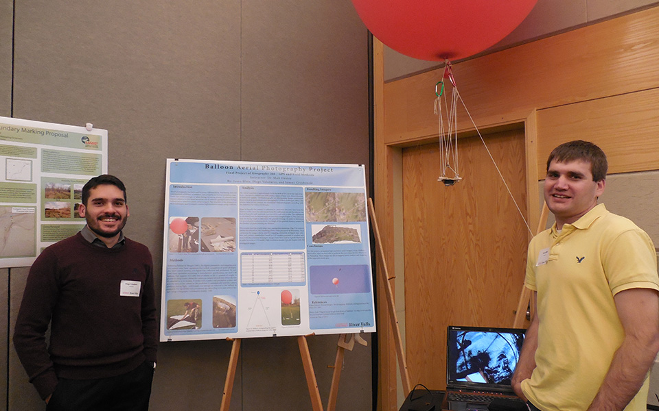Diego Valadares, left, and Jason Blatz, right, display their work from the semester at the Undergraduate Research, Scholarly and Creative Activity Fall Gala on Dec. 3. Blatz said that he had spent around seven hours the day before creating just one map for the poster.