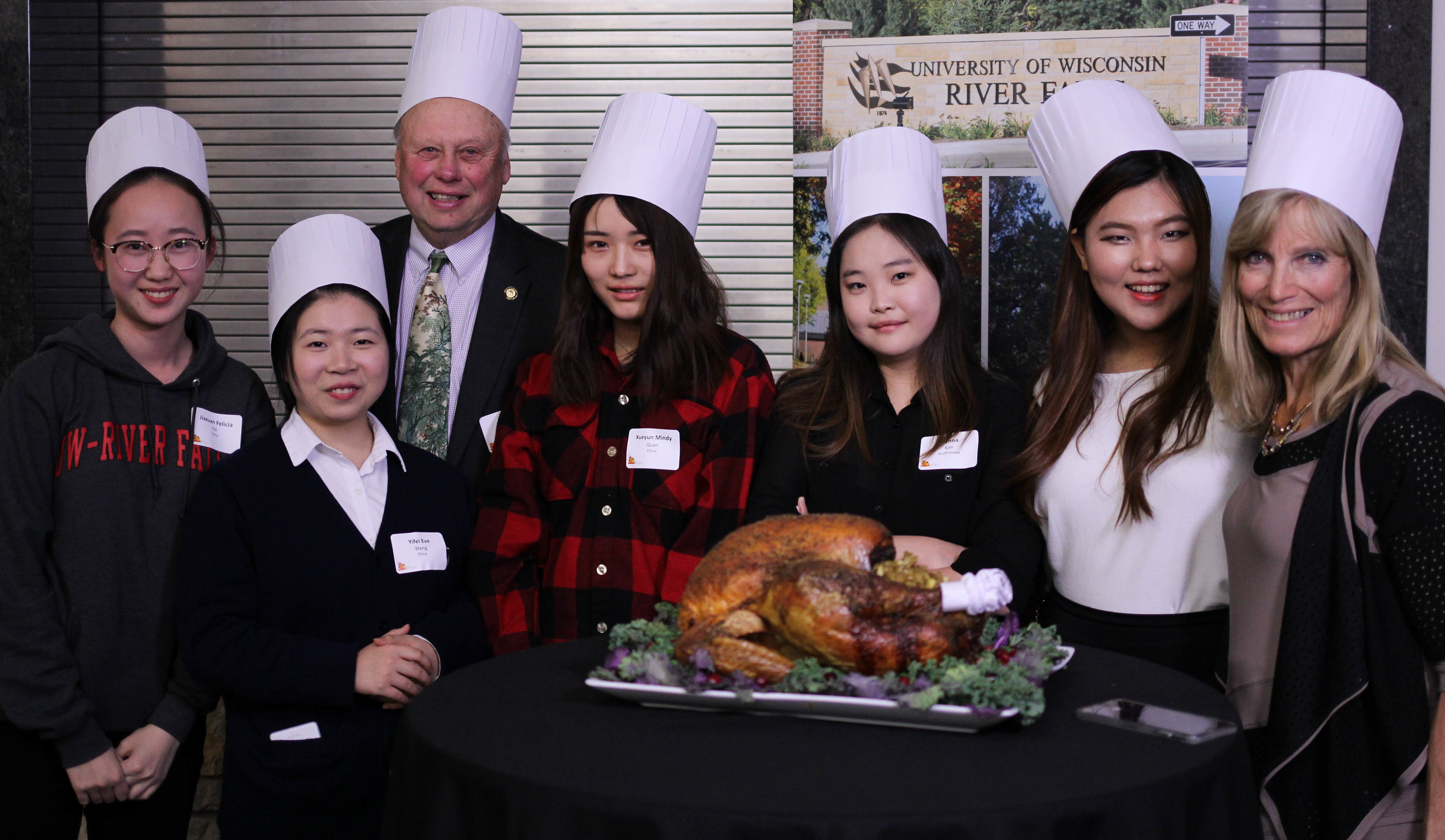 International students pose with their host family in front of the turkey at the International Thanksgiving dinner last year. (Photo by Chris Gregg for University Communications and Marketing)